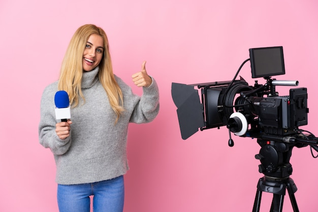 Reporter woman holding a microphone and reporting news over pink wall giving a thumbs up gesture