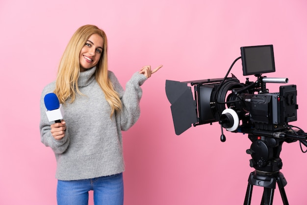 Reporter woman holding a microphone and reporting news over pink wall happy and pointing up