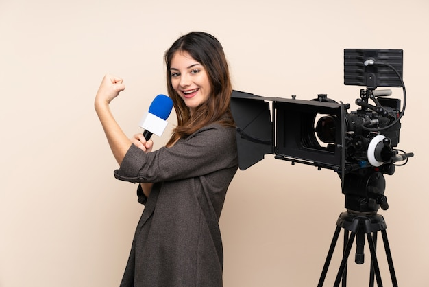 Reporter woman holding a microphone and reporting news over wall making strong gesture