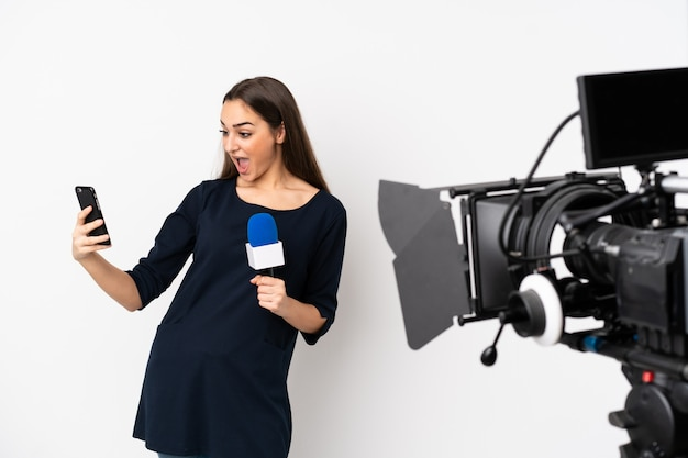 Reporter woman holding a microphone and reporting news on white wall making a selfie