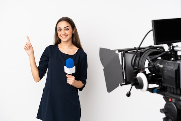 Reporter woman holding a microphone and reporting news on white wall showing and lifting a finger in sign of the best