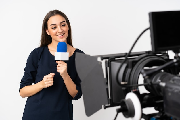 Reporter woman holding a microphone and reporting news on white wall