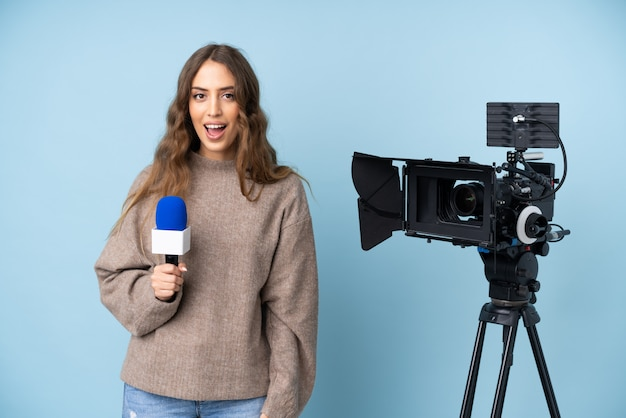 Reporter young woman holding a microphone and reporting news with surprise facial expression