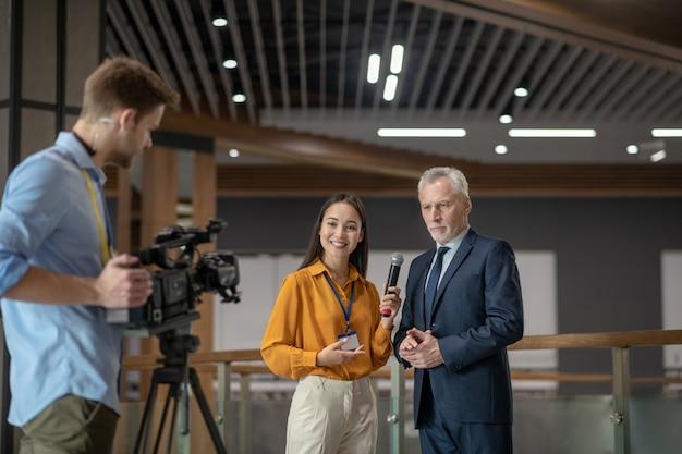 Репортеры с видеокамерой берут интервью у известного бизнесмена