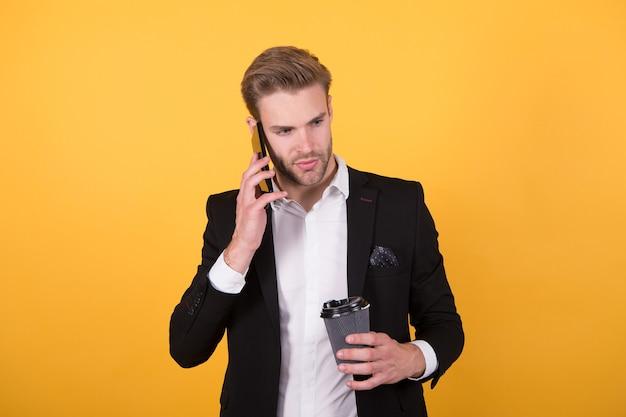 ニュースの報告。男はコーヒーを飲む電話の黄色の背景を話します。コーヒーを飲む。起業家がコーヒーを飲む理由。コーヒーブレイクのコンセプト。リラックスして楽しんでください。情報を聞くことに集中しました。