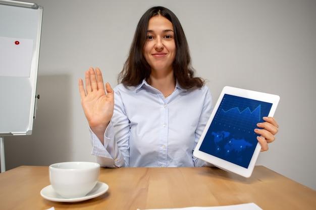 Составление отчетов. молодая женщина, работающая в режиме видеоконференции с коллегами, коллегами в офисе. интернет-бизнес, обучение во время изоляции от коронавируса и карантина. работа, финансы, современные технические концепции.