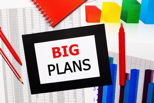 Отчеты и цветные диаграммы находятся на столе. также есть красные ручки, карандаш и бумага в черной рамке со словами большие планы. вид сверху