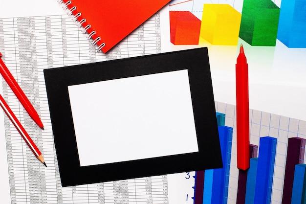 レポートとカラーチャートはテーブルの上にあります。赤ペン、鉛筆、コピースペース付きの紙もあります。上から見る