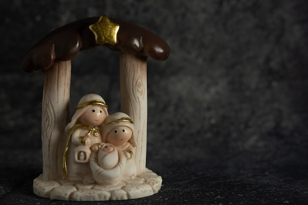 Representation of a christmas nativity scene with the small figures of baby jesus, mary and joseph on a rock background.