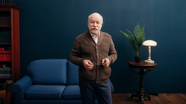 Representative elderly man poses in home office. bearded mature senior in living room, old age businessman
