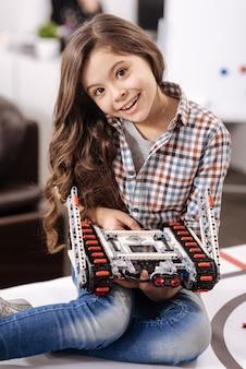 デジタル玩具を表す。ロボット工学研究室に座って、喜びを表現しながらデジタルロボットを保持している素敵な日当たりの良い喜んでいる女の子