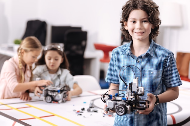 Representing our project. smiling delighted cheerful boy standing at school and holding robot while his classmates working on the project