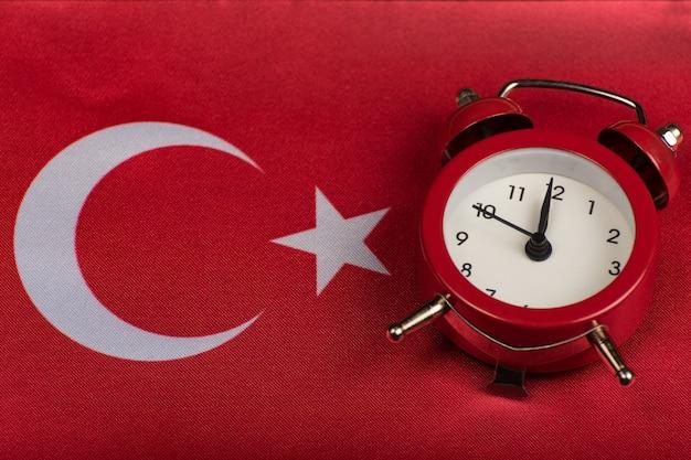 トルコ共和国の旗とビンテージの目覚まし時計をクローズアップ。トルコ語を学ぶ時間