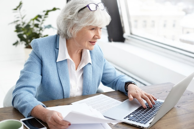 Reputable 65 year old female executive in stylish bkue suit enjoying wireless high speed internet connection while using laptop, analyzing accounts, holding papers in her hand, looking at screen