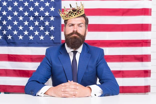 評判の良いビジネスマンハンサムな男は、机のアメリカ国旗の背景、ビッグボスの概念を座っています。