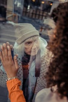 Request for help. portrait of an unhappy homeless woman asking for help while standing behind the window