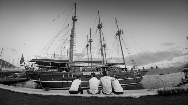 Rera view image of people sitting on bench at sea port and looking on moored historical wooden ship