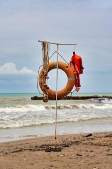 Спасательное оборудование на воде, спасательный круг и спасательный жилет на пляже