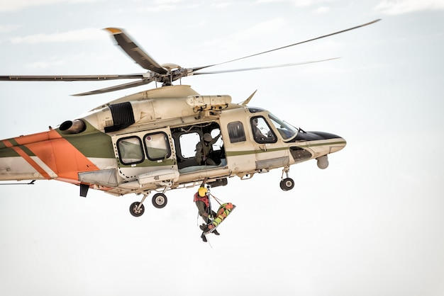Rescue helicopter in flight winching rescuer