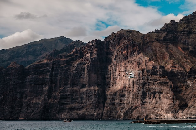 Rescue helicopter flying between the cliffs of los gigantes
