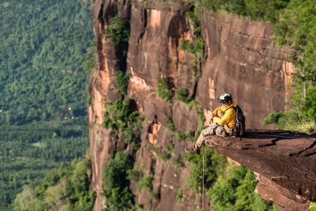 バックパックを持ったレスキューハイカーは、自然の岩壁を登ります。登山用品ロープカラビナ着用