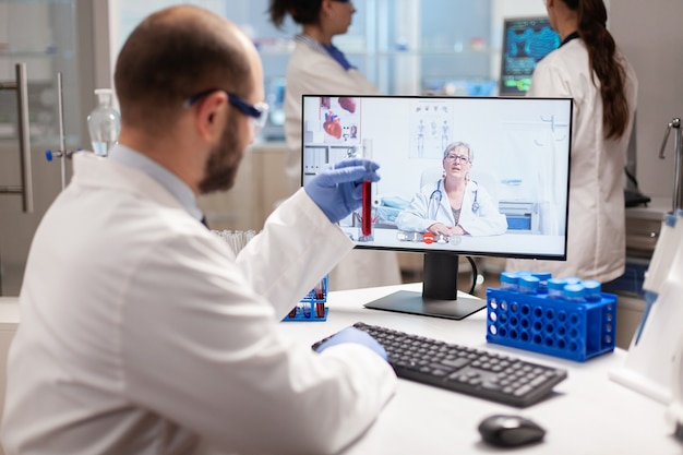 Reseacher holding blood sample discussing treatment with doctor during virtual video call