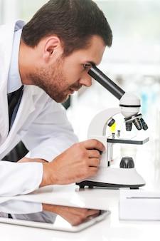 연구 및 개발. 그의 작업 장소에 앉아있는 동안 현미경을 사용하여 흰색 유니폼에 집중된 젊은 과학자의 측면보기