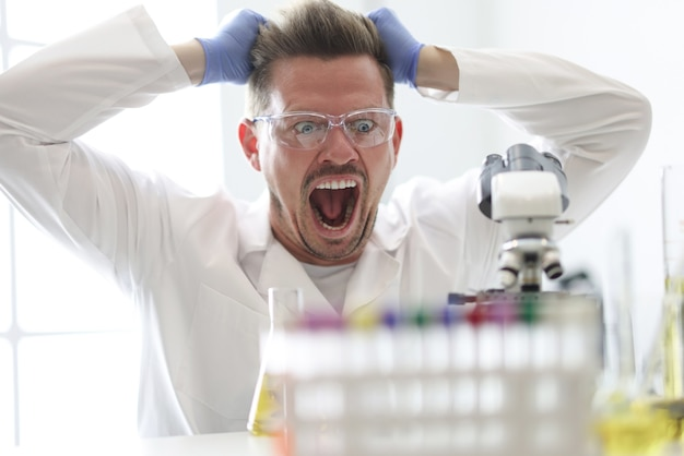 Research assistant looks enthusiastically at microscope closeup