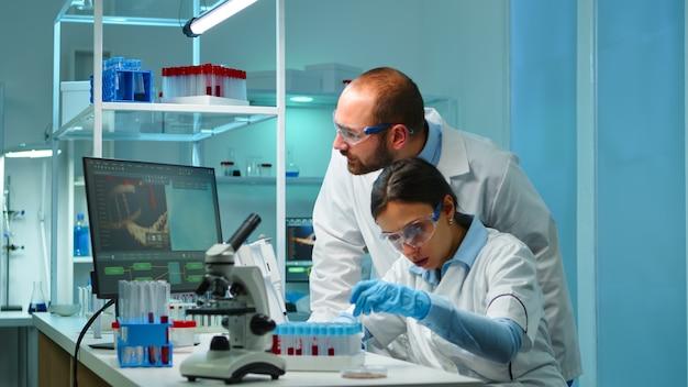 현대 장비를 갖춘 실험실에서 특수 프로그램으로 혈액 및 유전 물질 샘플을 분석하는 첨단 기술로 실험실에서 밤에 일하는 연구 화학자. 바이러스 진화를 조사하는 팀