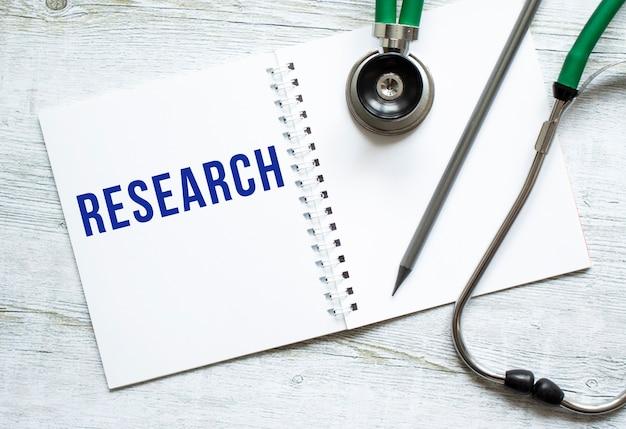 Исследование записано в блокноте на светлом деревянном столе рядом с карандашом и стетоскопом.