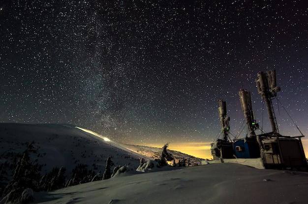 雲ひとつない星空の夜、山の斜面に研究科学拠点があります