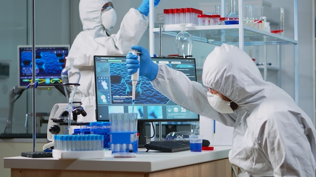 Research scientist in protection suit using micropipette filling test tubes in lab. team of microbiologists examining virus evolution using high tech analysing treatment development against covid19.