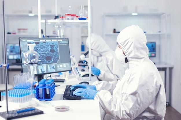 Ученый-исследователь печатает информацию, полученную в современной лаборатории. медицинский инженер, использующий компьютер во время глобальной пандемии коронавируса, одетый в комбинезон.