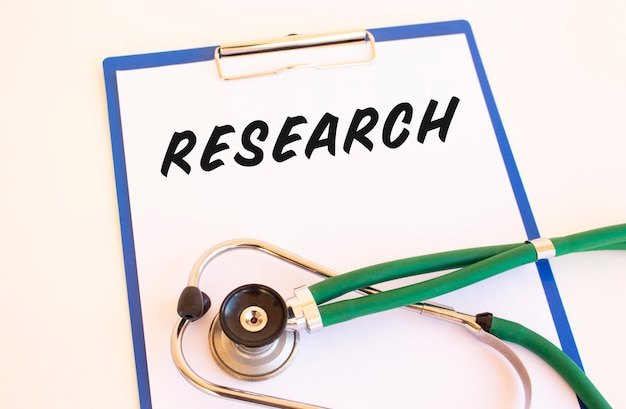 Research - text on medical folder with documents and stethoscope