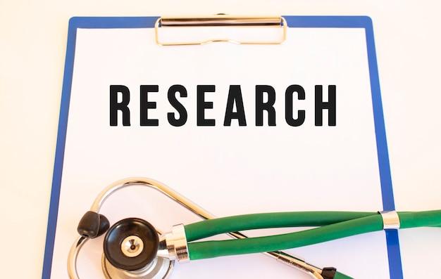 Исследования - текст на медицинской папке с документами и стетоскопом на белом фоне. медицинская концепция.