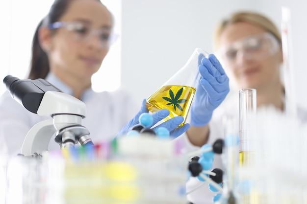 研究者と同僚は、金色の液体が入ったフラスコの手で実験室で研究を行っています...