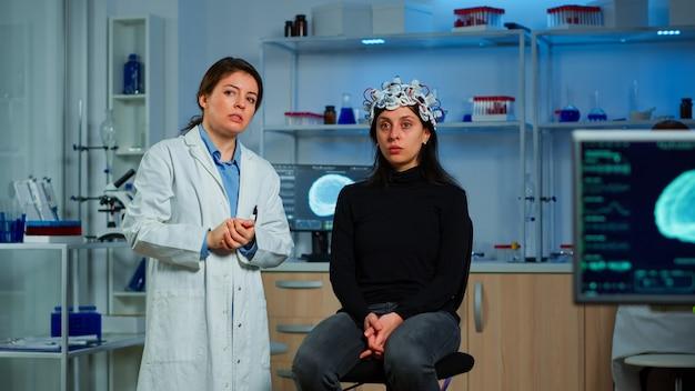 神経学的研究室で医療革新を使用してタッチスクリーン、仮想現実を備えた仮想ディスプレイを見ている脳波ヘッドセットを持つ研究者と患者。ヘルスケアシミュレーターを使用する科学者