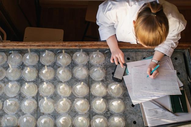 研究室で彼女の職場で電卓で研究室の計算を計算する研究者。