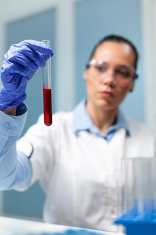 Researcher doctor holding transparent test tube with blood working at biochemistry experiment