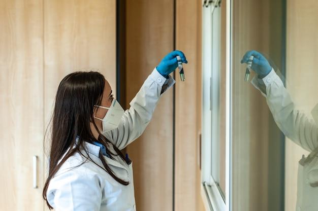 研究室で医療用チューブを扱う研究者の医師の科学者または実験助手