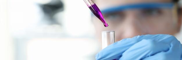 Исследователь капает фиолетовую жидкость из пипетки в пробирку научные исследования химии