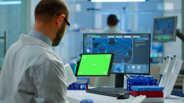 연구원은 현대적인 장비를 갖춘 실험실에서 크로마 키 디스플레이가 있는 태블릿을 들고 보고 있습니다. 백신 연구를 하는 미생물학자 팀은 녹색 화면, 격리된 모형 디스플레이가 있는 장치에 글을 쓰고 있습니다.