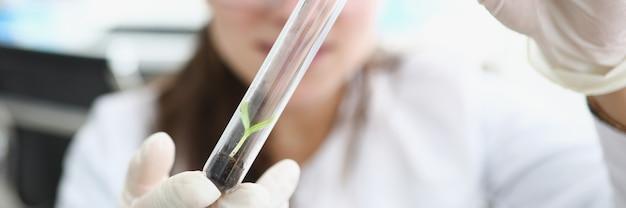 연구원은 손에 지구와 작은 식물이 있는 플라스크를 들고 있습니다.