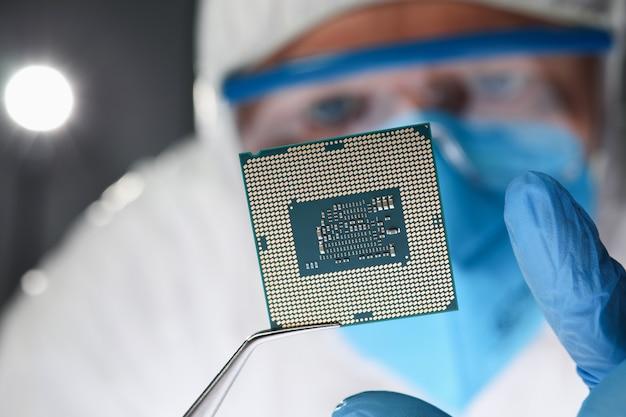 Исследователь держит небольшую микросхему с щипцами крупным планом