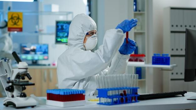 Исследователь в комбинезоне держит пробирки с образцом крови для нового лечения в медицинской лаборатории. команда врачей изучает эволюцию вируса с помощью высоких технологий для разработки вакцины против covid19