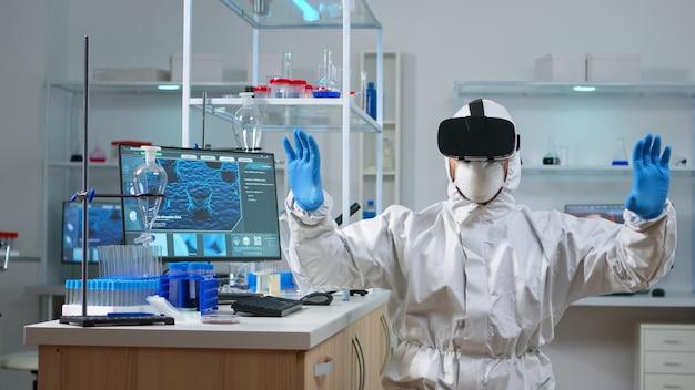 Исследователь в защитном костюме, использующий vr, работает в химической лаборатории. команда биологов изучает эволюцию вакцины с помощью высоких технологий и технологий, исследует лечение против вируса covid19