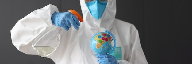 보호 복을 입은 연구원은 소독제와 글로브를 들고 있습니다. 세계 개념의 코로나 바이러스 전염병