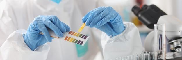 Исследователь в защитном костюме держит химические реактивы образцов. концепция химического анализа
