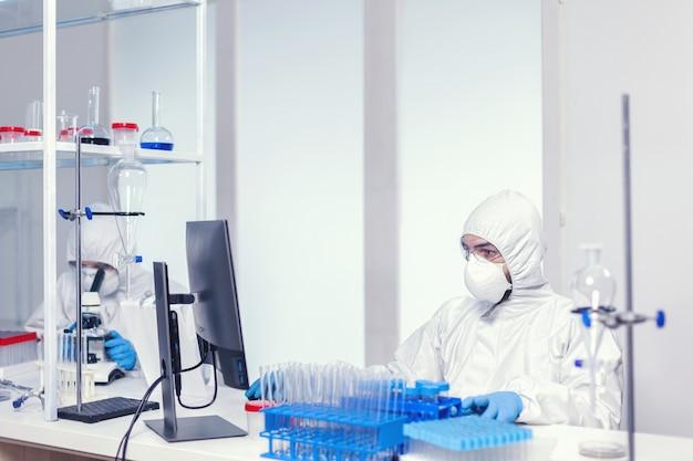 Исследователь в стерильном костюме сидит на рабочем месте в исследовательской лаборатории covid19. медицинский инженер, использующий компьютер во время глобальной пандемии коронавируса, одетый в комбинезон.