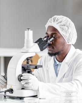 Исследователь в лаборатории биотехнологии с микроскопом